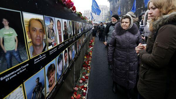 Uczestnicy Ogólnoukraińskiego Ludowego Wiecu składają kwiaty pod zdjęciami poległych na Placu Niepodległości w Kijowie - Sputnik Polska