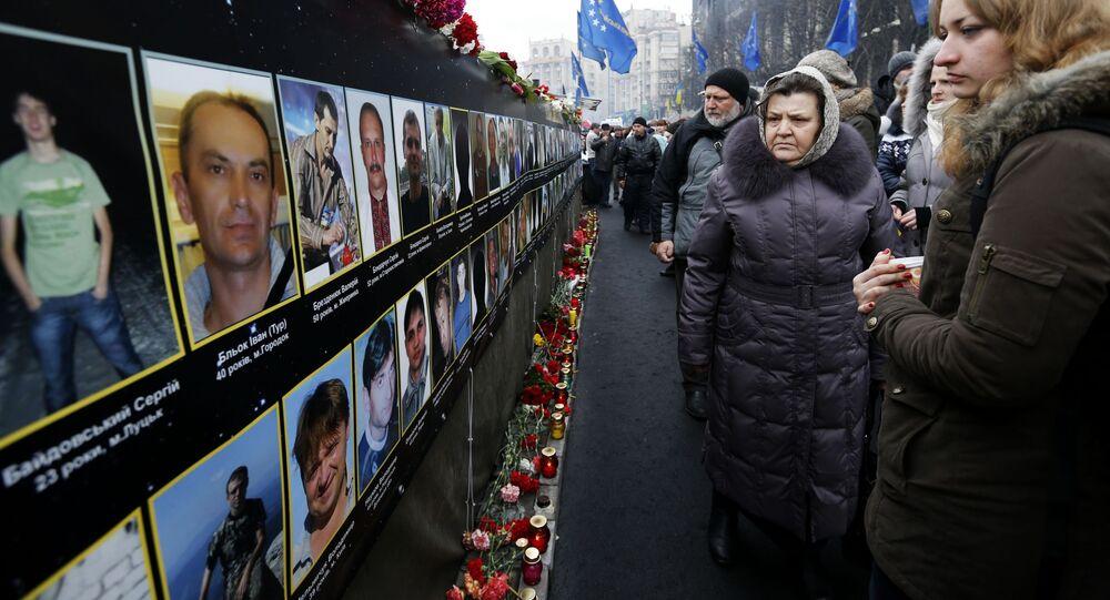 Uczestnicy Ogólnoukraińskiego Ludowego Wiecu składają kwiaty pod zdjęciami poległych na Placu Niepodległości w Kijowie