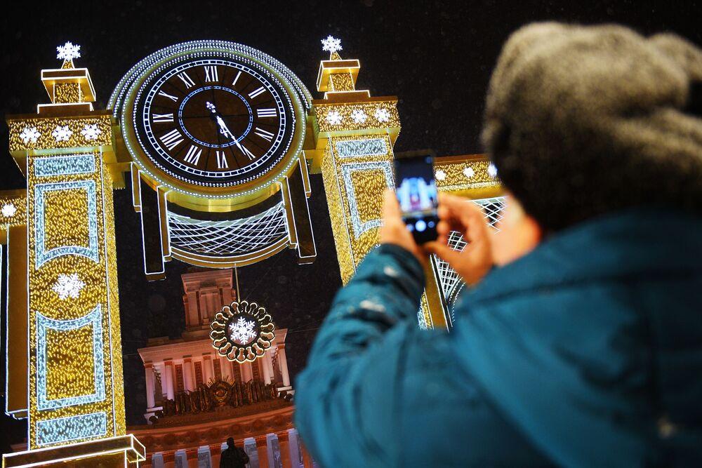 """Zwiedzający Ogólnorosyjskiego Centrum Wystawowego fotografuje zegar """"Czas Bożego Narodzenia"""", zainstalowany przez Pawilonem Głównym."""