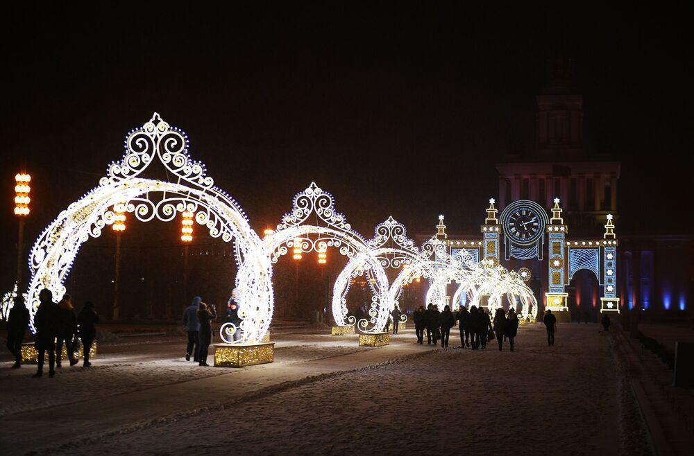 """Arki z girlandami i zegar """"czas Bożego Narodzenia"""", ustawione przed Pawilonem Głównym w Ogólnorosyjskim Centrum Wystawowym."""