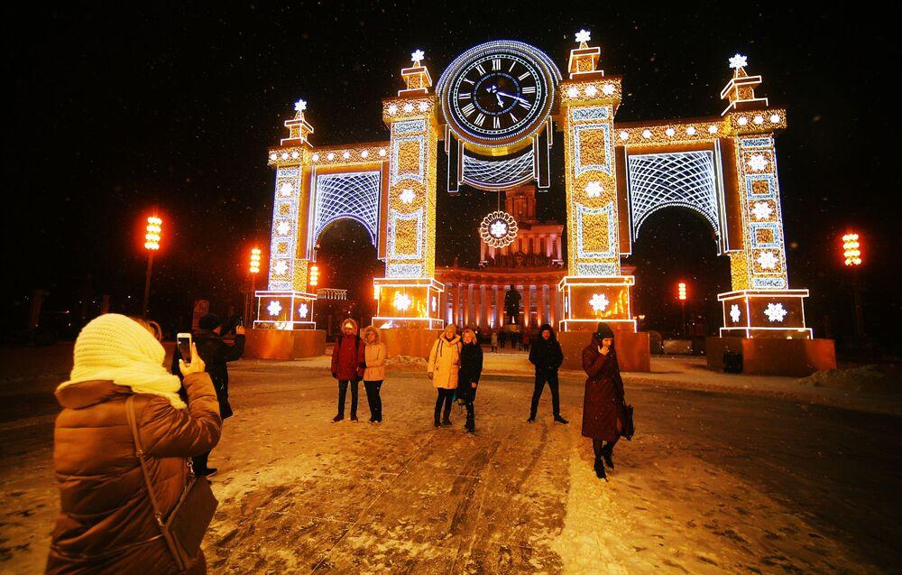 """Zwiedzający Ogólnorosyjskiego Centrum Wystawowego robią sobie zdjęcie obok zegara """"Czas Bożego Narodzenia"""" przed Pawilonem Głównym."""