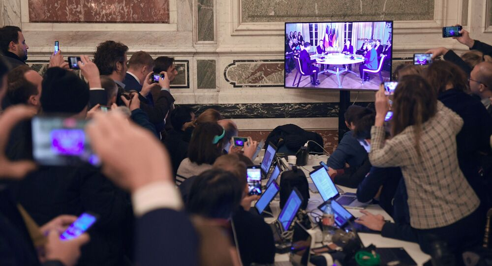 Dziennikarze oglądają transmisję szczytu normandzkiego podczas dwustronnych spotkań szefów państw.
