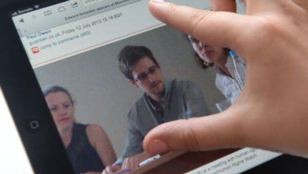 Dziennikarz patrzy na ekran komputera, na którym jest zdjęcie byłego pracownika CIA Edwarda Snowdena - Sputnik Polska