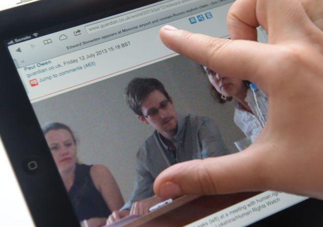 Dziennikarz patrzy na ekran komputera, na którym jest zdjęcie byłego pracownika CIA Edwarda Snowdena