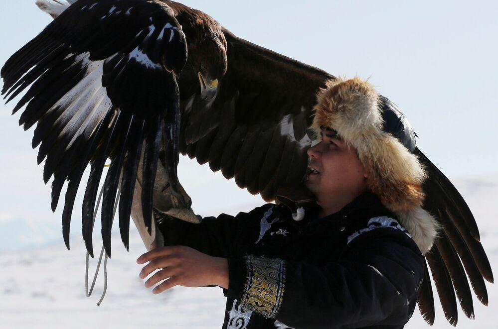 Myśliwy trzyma oswojonego złotego orła podczas tradycyjnego polowania w Kazachstanie