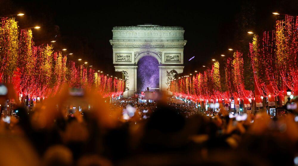 Widzowie podczas świątecznego pokazu świetlnego pod Łukiem Triumfalnym w Paryżu.
