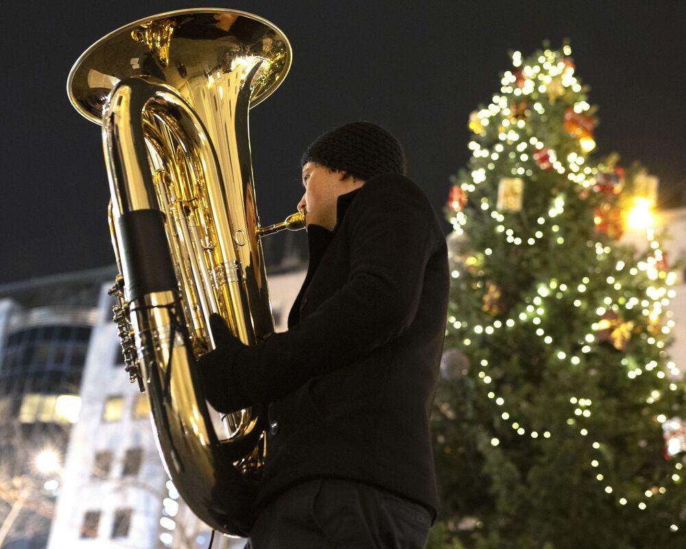Muzyk orkiestry dętej Rudersdorf Music Society gra na trąbce na jarmarku bożonarodzeniowym w Wiedniu.