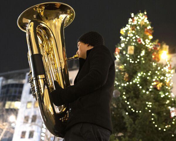 Muzyk orkiestry dętej Rudersdorf Music Society gra na trąbce na jarmarku bożonarodzeniowym w Wiedniu - Sputnik Polska