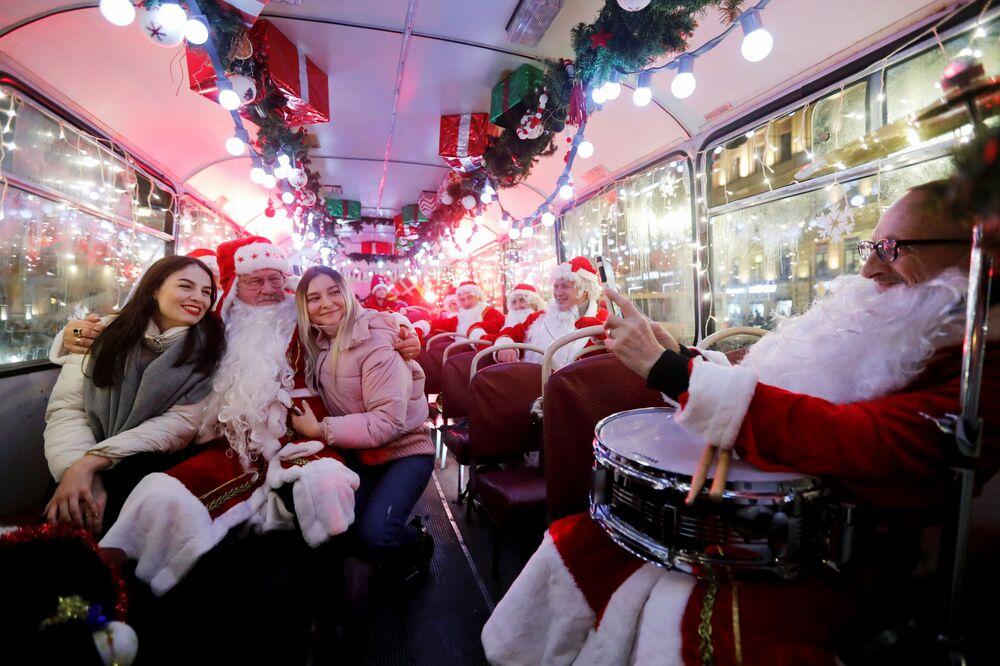 Muzykanci w kostiumach Mikołajów w autobusie, Petersburg