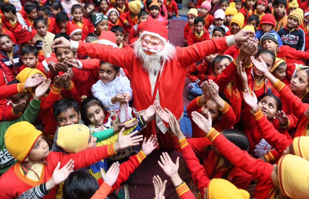 Dziewczyna w kostiumie Mikołaja rozdaje prezenty dzieciom w Indii