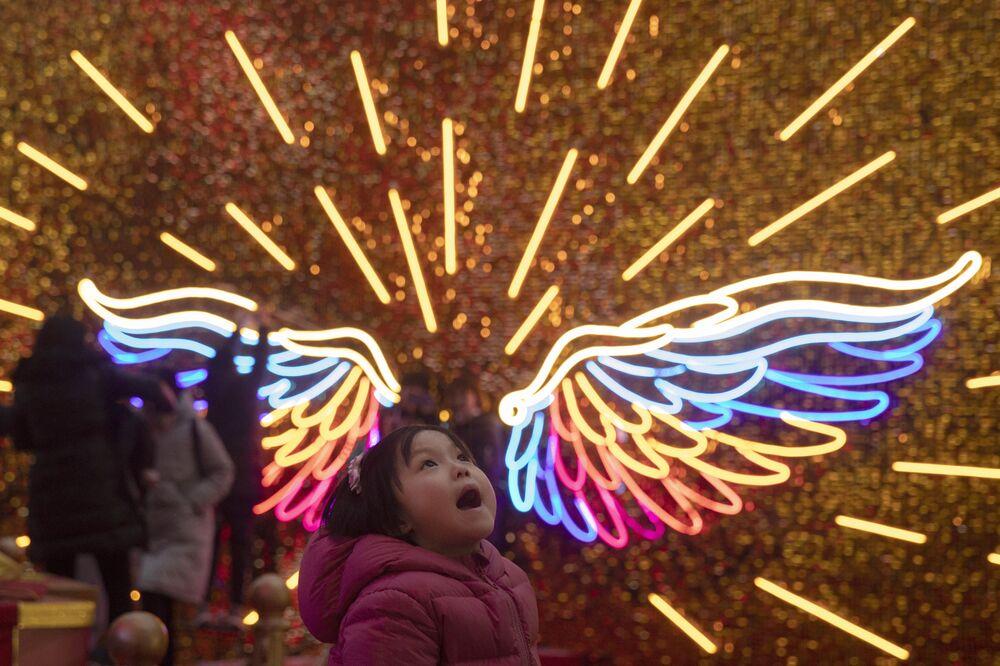 Dziewczynka spaceruje w świątecznie oświetlonym parku w Pekinie