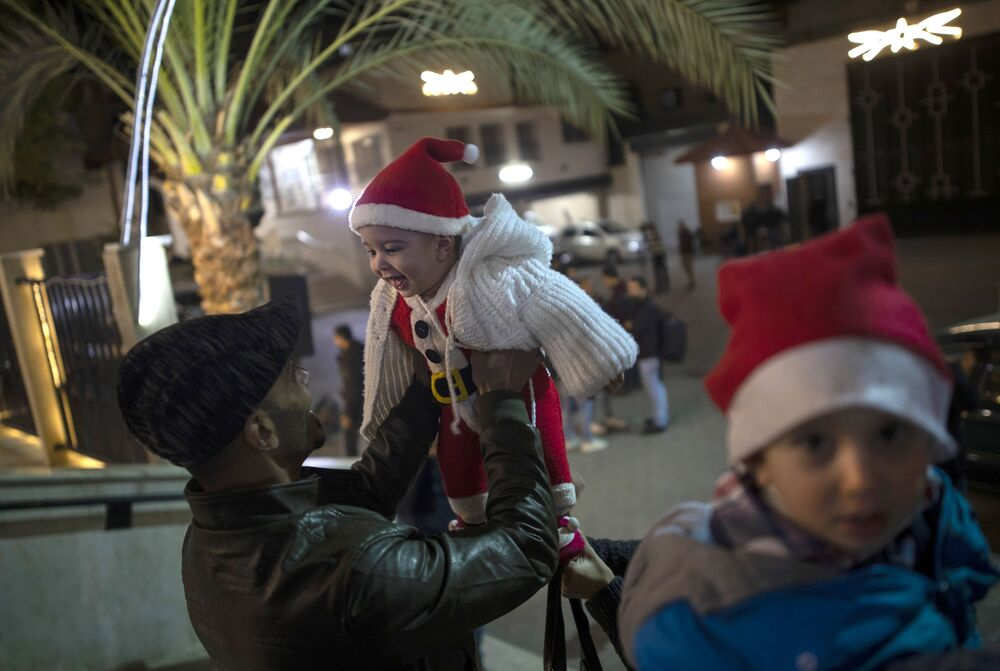 Mężczyzna bawi się z dzieckiem przed rozpoczęciem mszy w Gazie