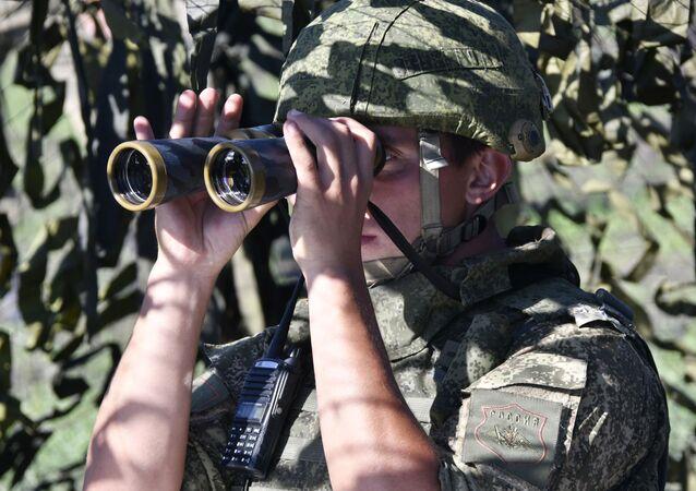 Żołnierz w punkcie kontroli ognia podczas taktycznych ćwiczeń artyleryjskich na poligonie Molkino w Kraju Krasnodarskim