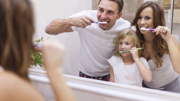 Rodzina czyści zęby przed lustrem w łazience. - Sputnik Polska