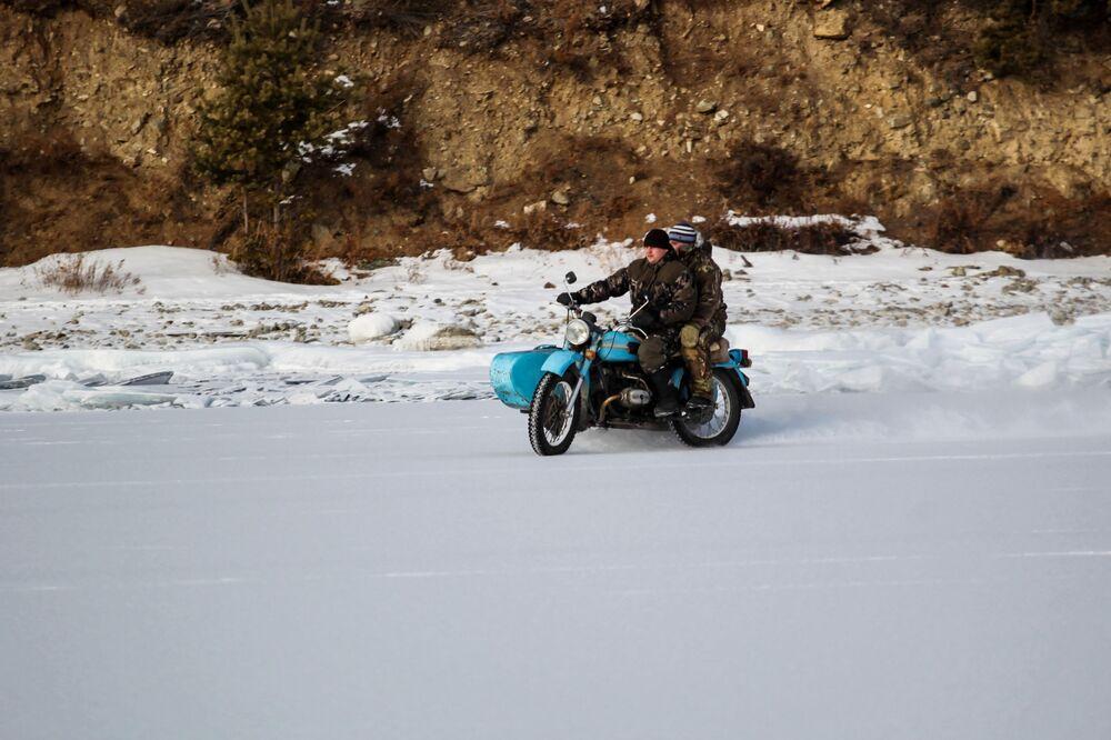 Mieszkańcy pobliskiej wsi jadą na motocyklu nad brzegiem jeziora Bajkał