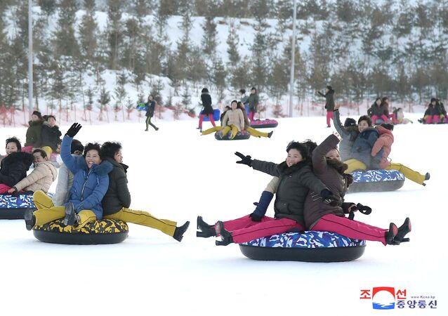 Ludzie zjeżdżają z górek na terenie kurortu Yangdok w Korei Północnej