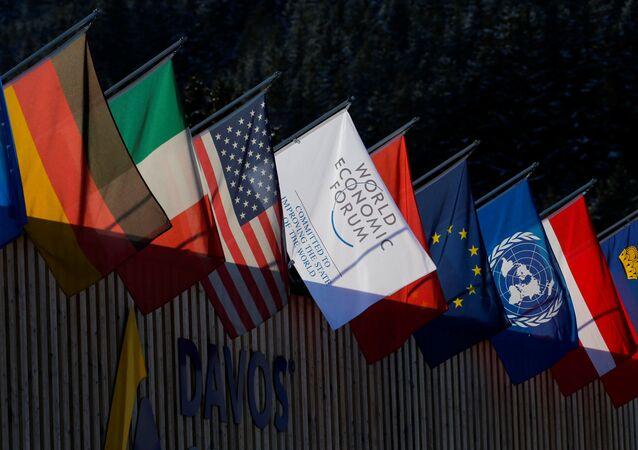 Flagi narodowe kilku państw i logotyp Światowego Forum Ekonomicznego w Davos