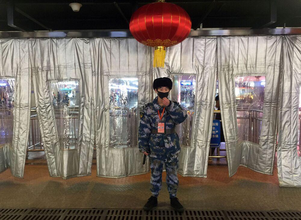 Ochroniarz w masce na dworcu w Pekinie