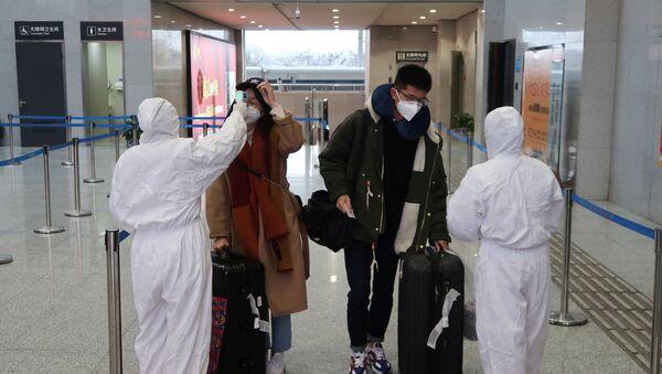 Pracownicy medyczni mierzą temperaturę pasażerów na lotnisku w Chinach - Sputnik Polska