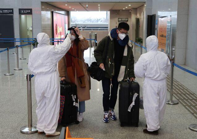 Pracownicy medyczni mierzą temperaturę pasażerów na lotnisku w Chinach