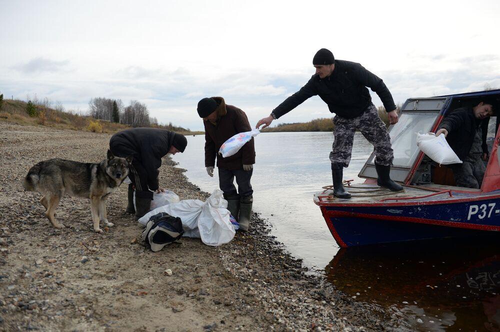 Meszkańcy miejscowości Szaburowo w obwodzie swierdłowskim pomagają pracownikom poczty wyładować kuter