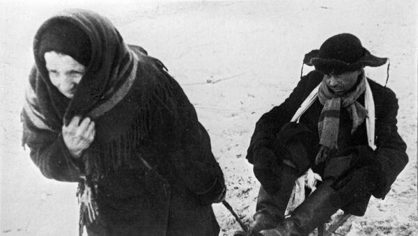 Kobieta wiezie osłabionego z głodu męża na sankach podczas blokady Leningradu  - Sputnik Polska