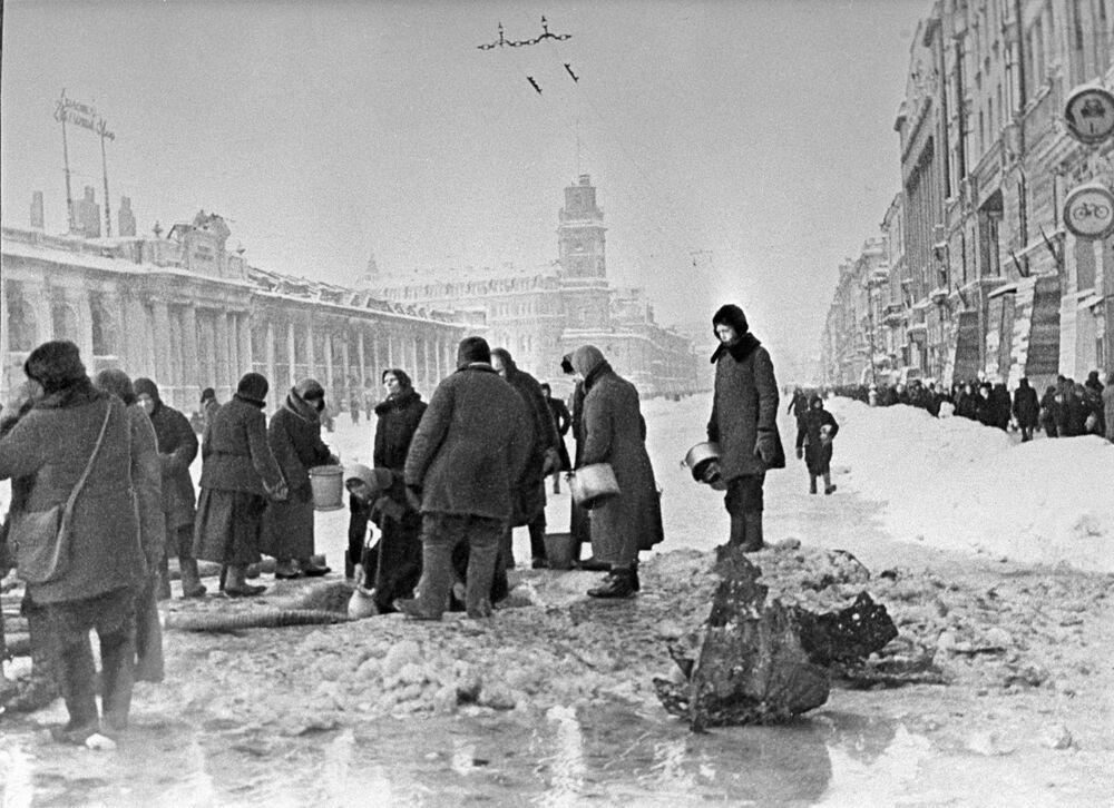 Mieszkańcy nabierają wodę, która pojawiła się po ostrzelaniu asfaltu podczas blokady Leningradu