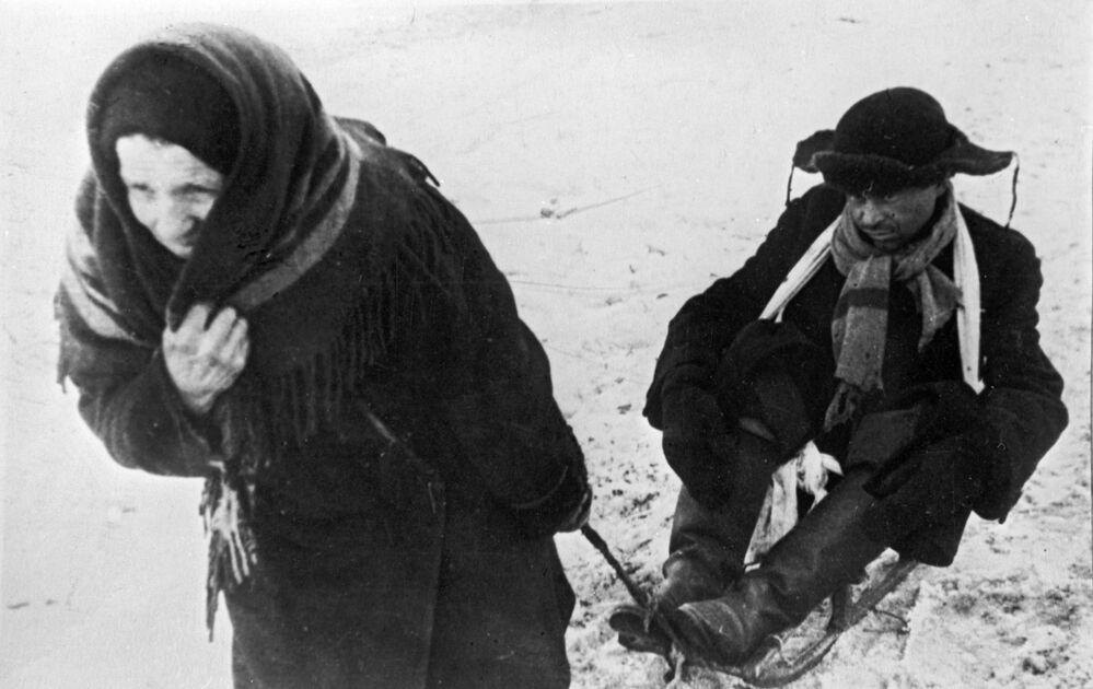 Kobieta wiezie osłabionego z głodu męża na sankach podczas blokady Leningradu