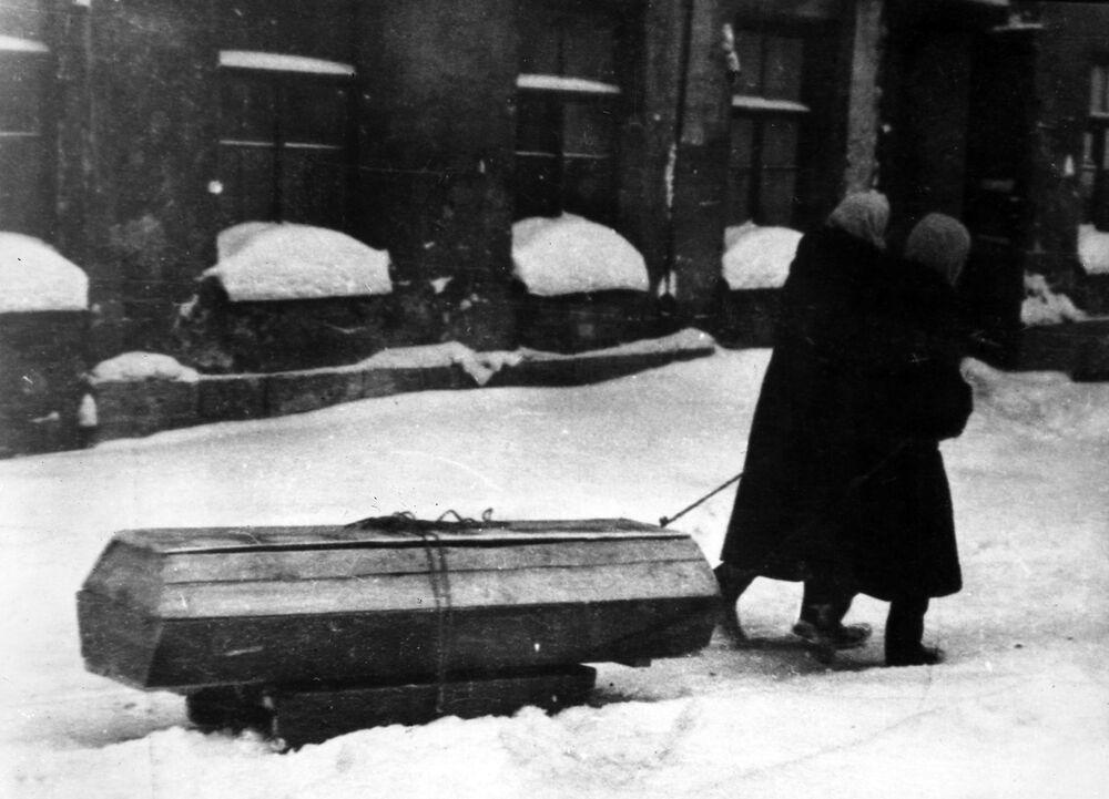 Cywile wiozą na sankach trumnę ze zmarłym podczas blokady Leningradu