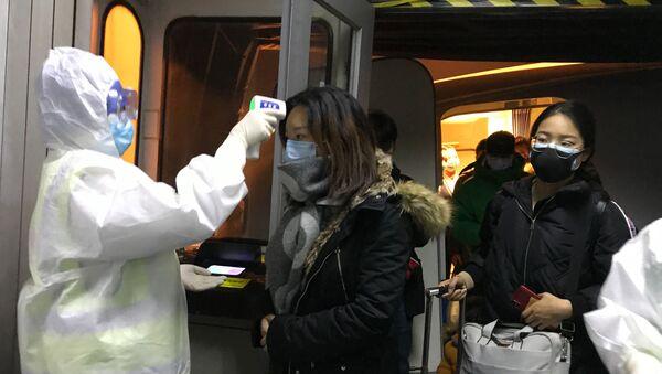 Pracownicy medyczni w kombinezonach ochronnych sprawdzają temperaturę ciała pasażerów przylatujących z Wuhan do Pekinu - Sputnik Polska