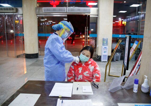 Pielęgniarka mierzy temperaturę pacjentki w szpitalu w okręgu Yueyang w chińskiej prowincji Hunan
