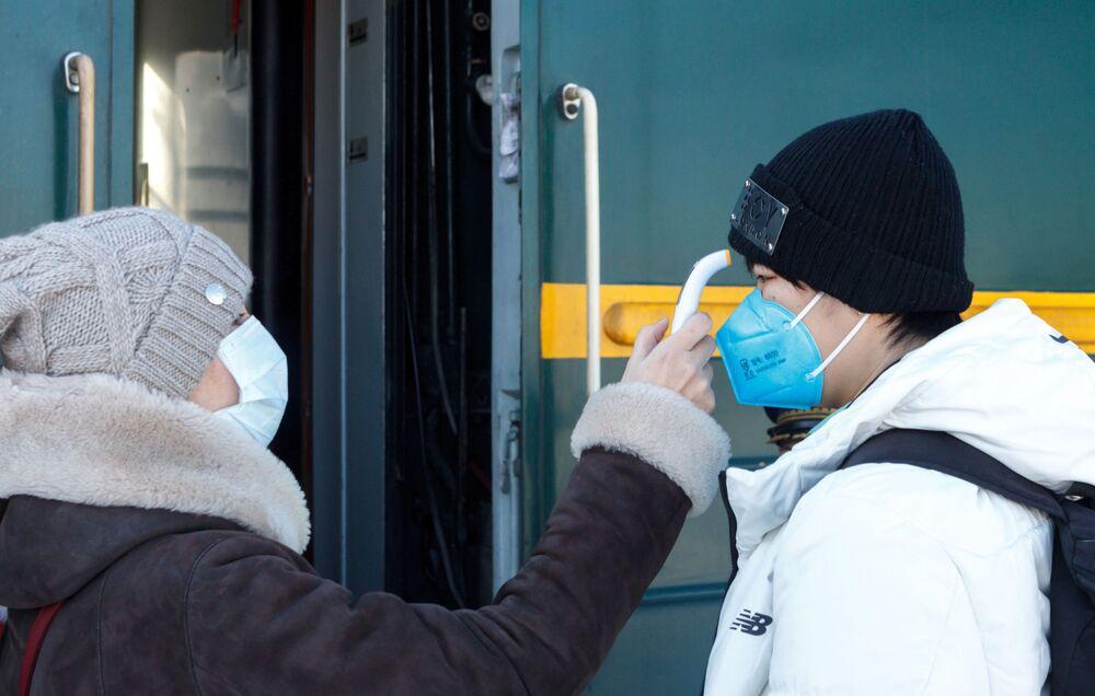 Specjalista medyczny bada pasażera pociągu Pekin-Moskwa na stacji kolejowej Irkuck-Pasażerski.
