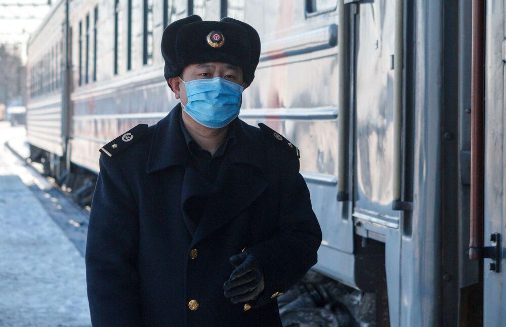 Konduktor w pociągu nr 4 Moskwa-Pekin na peronie w Irkucku.