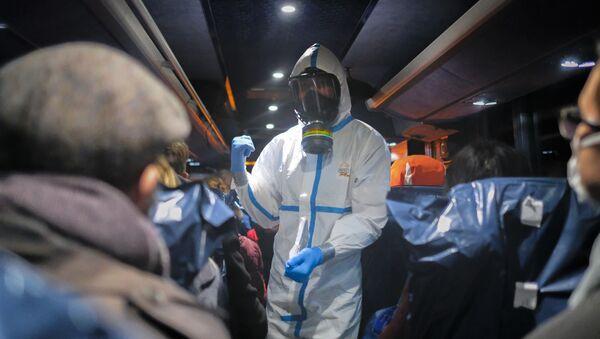 Oficer w kombinezonie ochronnym instruuje ludzi ewakuowanych z Wuhan  - Sputnik Polska