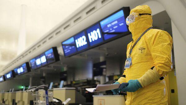 Pracownik w kostiumie ochronnym w porcie lotniczym, Wuhan  - Sputnik Polska