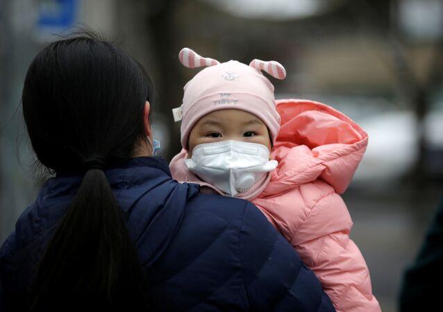 Kobieta z dzieckiem w maskach medycznych na jednej ulic w Pekinie
