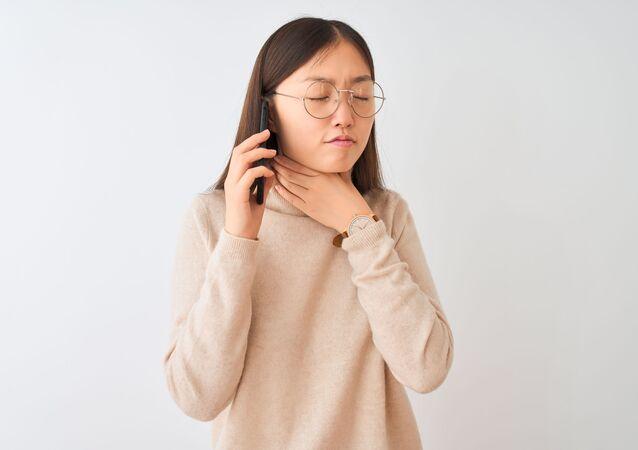 Kobieta ze smartfonem trzymająca się za gardło
