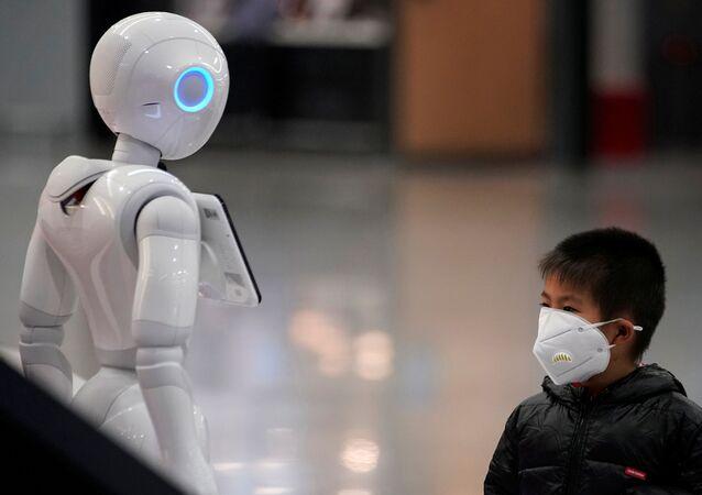 Dziecko w masce ochronnej przyglądający się robotowi na lotnisku międzynarodowym w Szanghaju
