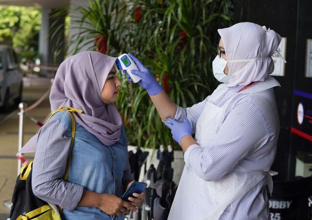 Pielęgniarka w szpitalu mierzy temperaturę obywatelce Malezji ewakuowanej z Chin