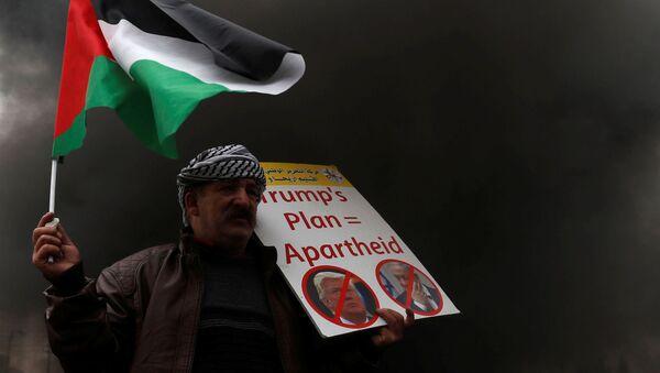 Protestujący trzyma w ręku palestyńską flagę w czasie akcji protestu przeciwko USA - Sputnik Polska