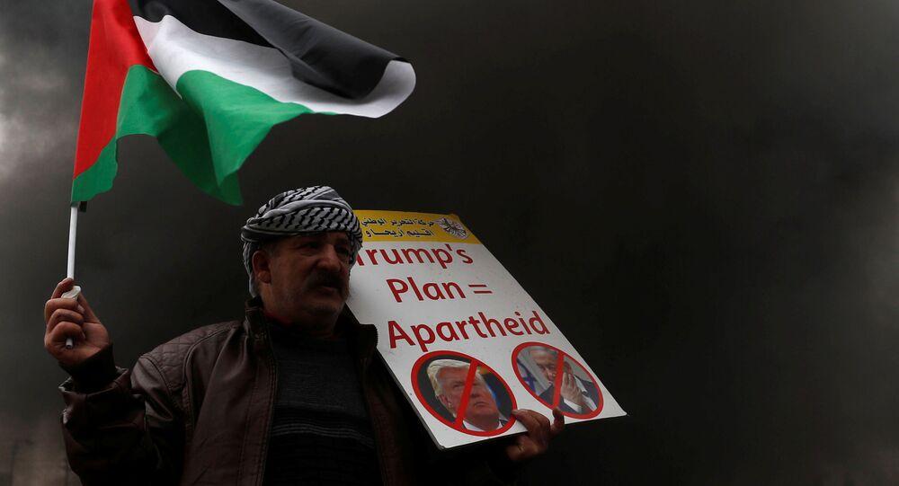 Protestujący trzyma w ręku palestyńską flagę w czasie akcji protestu przeciwko USA