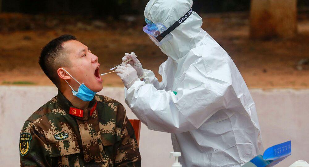 Sanitariusz pobiera próbkę od policjanta w celu wykonania testu na koronawirusa po jego powrocie z wakacji w Chinach