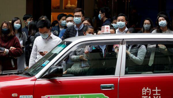 Ludzie w maskach ochronnych na ulicach Hongkongu - Sputnik Polska