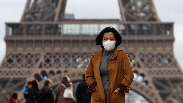 Kobieta w masce ochronnej pod wieżą Eiffla w Paryżu, Francja - Sputnik Polska