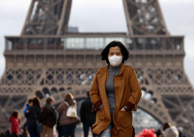 Kobieta w masce ochronnej pod wieżą Eiffla w Paryżu, Francja