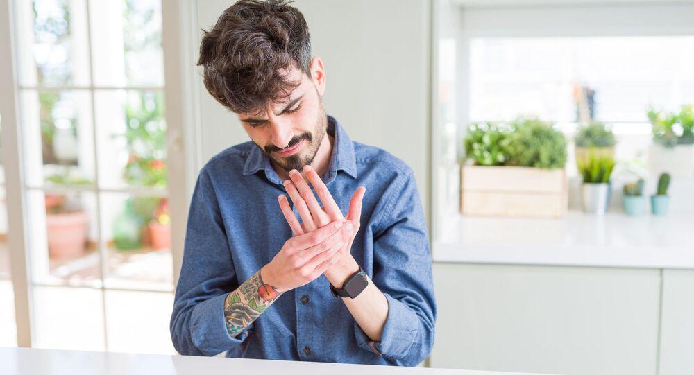 Mężczyzna trzyma się za chorą rękę