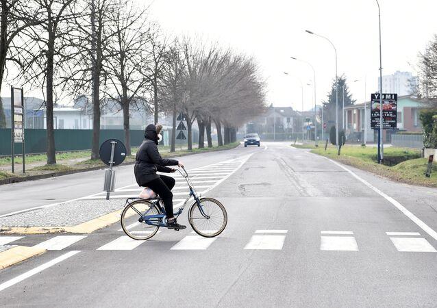 Człowiek w maseczce na rowerze w zamkniętym w związku z kwarantanną mieście Codogno