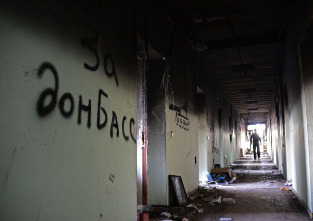Napis na murze w podpalonym budynku rady miejskiej w Mariupolu