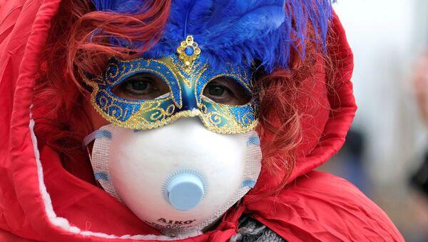 Посетитель Венецианского карнавала в праздничной и медицинской масках - Sputnik Polska