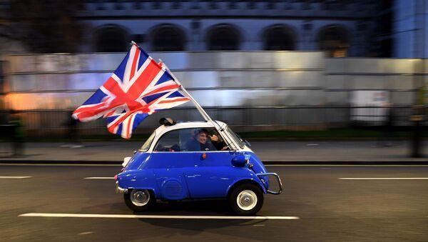 Mężczyzna z flagami Wielkiej Brytanii w centrum Londynu w dzień oficjalnego wyjścia kraju z UE - Sputnik Polska